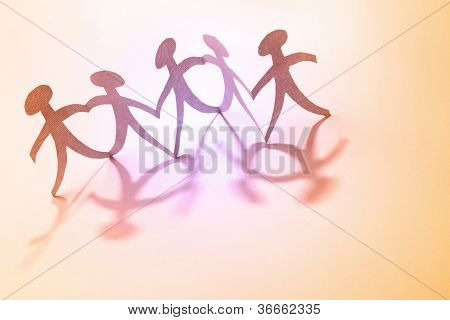 Team of paper doll people holding hands. Teamwork concept