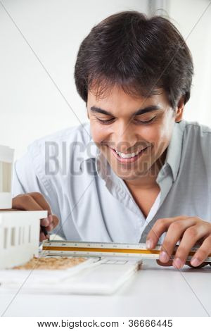 Skilled young male architect completing a design at the drawing board with ruler