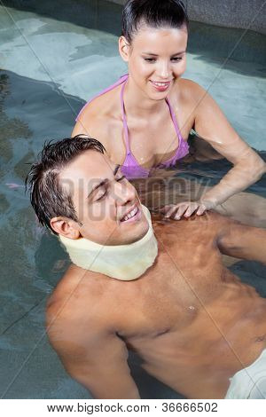 Young man wearing neck brace in pool with beautiful woman