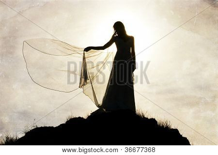 Silhouette of romantic woman on field with veil in the wind