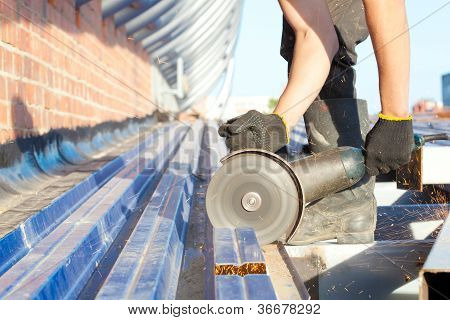 Industrial worker sawing steel sheet