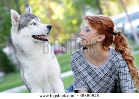 young happy woman and haski dog outdoors on natural background