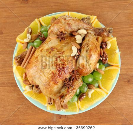 whole roasted chicken with grapes, oranges and spices on blue plate on wooden background close-up