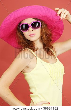 Smiling beautiful girl with beach hat and glasses on pink background
