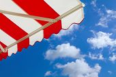 picture of awning  - Red and white Awning over bright sunny blue sky - JPG