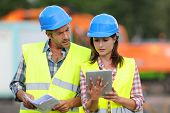 stock photo of real-estate-team  - Construction people using electronic tablet on site - JPG