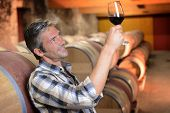Winemaker checking red wine quality in wine cellar