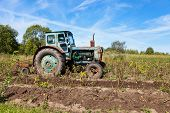 stock photo of last day work  - Old tractor in the field in last summer - JPG