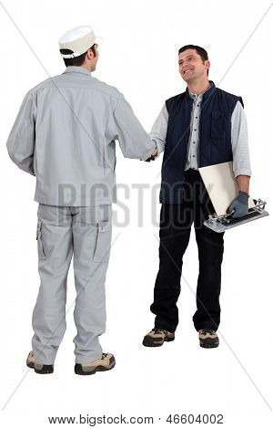 tile cutter shaking hands with other worker