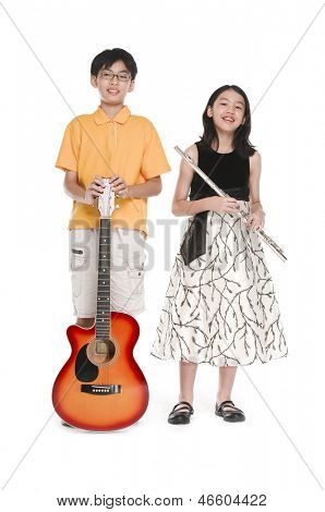 Portrait of brother and sister playing transverse flute with holding a classical guitar