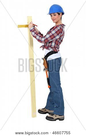 Woman measuring the width of a plank of wood