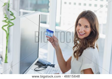 Cheerful brunette designer purchasing online with her credit card