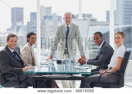 Cheerful team of business people in the meeting room with the boss standing in the middle