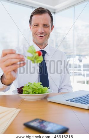 Cheerful businessman eating a salad during the lunch time