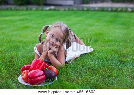 Lovely Girl With Pigtails In A Garden With A Plate Of Vegetables