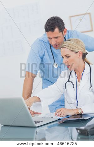 Blonde woman showing something on a laptop to her colleague in a medical office
