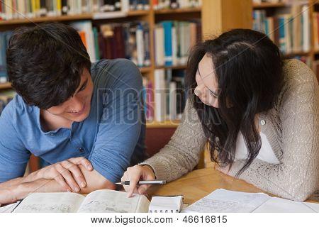 Zwei Schüler sitzen an einem Schreibtisch in einer Bibliothek, während sie lernen und schreiben