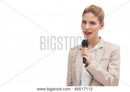 Frowning businesswoman with microphone on a white background