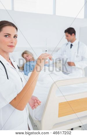Doctor with a syringe in front of hospitalized woman and doctor