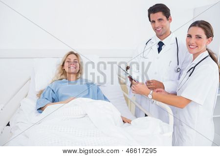 Smiling patient and doctors in a bedroom