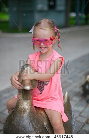 Little Girl Astride On A Duck Figure Of Iron And Having Fun