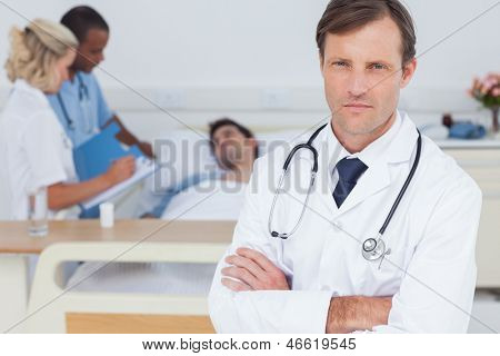 Serious doctor standing and looking at the camera in front of his colleagues and a patient