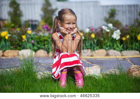 Beautiful Girl Sitting In Her Garden And Laughting