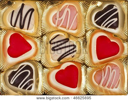 chocolate and marzipan hearts candies on golden  textured background