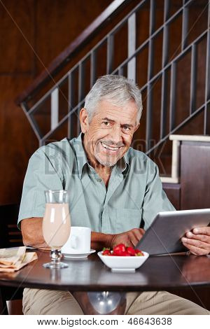 Happy senior man with tablet computer sitting in a caf���©
