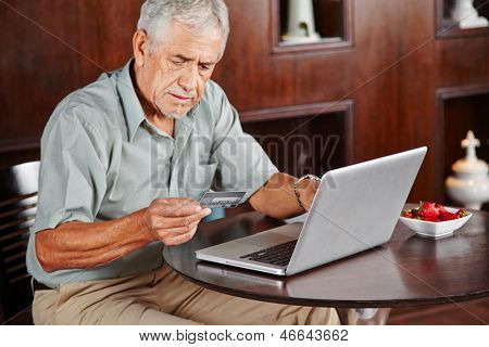 Senior man at laptop paying with credit card for online shopping