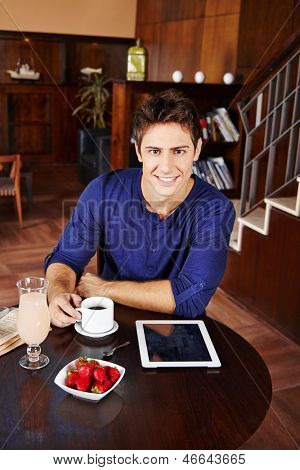 Man eating breakfast in caf���© with cup of coffee