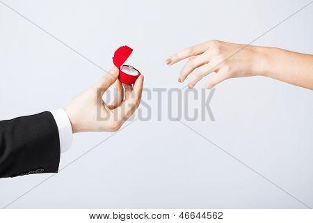 couple hands with wedding ring and gift box.