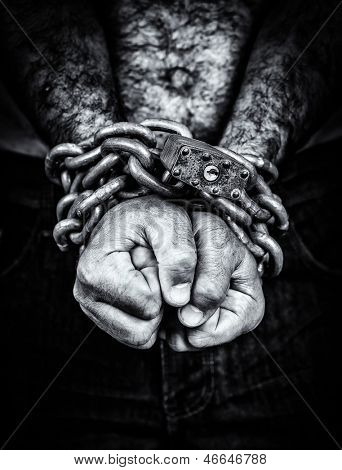 Dramatic black and white image of the hands of a shirtless  man chained with an iron chain and a padlock (emerging from a black background)