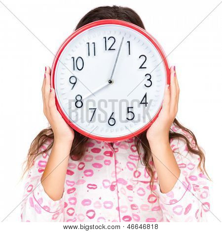 Child wearing pink pajamas holding a clock in place of her face (isolated on white)