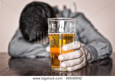 Black and white image of a sleeping drunk man (only his beer is in color)
