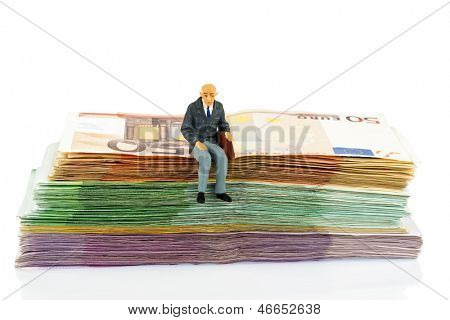 symbolic photo for retirement and old age, figure of an old man sitting on a pile of banknotes