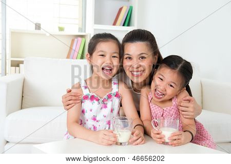Happy Asian mother and daughters drinking milk at home. Parent and children. Beautiful family model.
