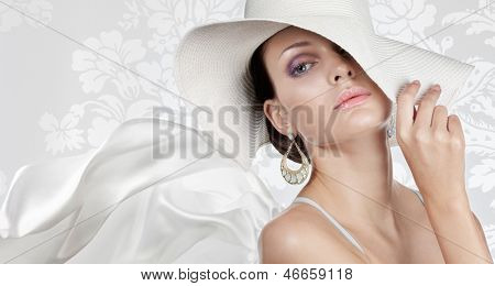 Elegant woman in white hat on white fancy background
