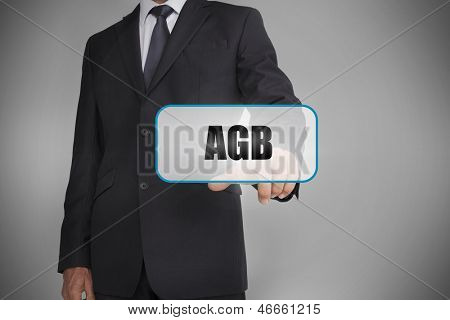 Businessman touching white tag with the word agb written on it on grey background
