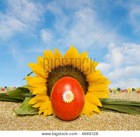 Easter Red Decorated Egg And Sunflower Over Blue Sky