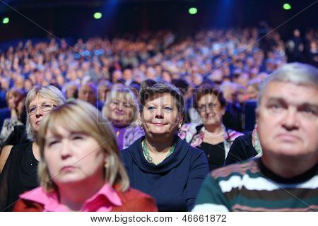MOSCOW - OCTOBER 14: Smiling woman and other spectators listen song at anniversary concert of Edyta Piecha in Kremlin Palace, on October 14, 2012 in Moscow, Russia.