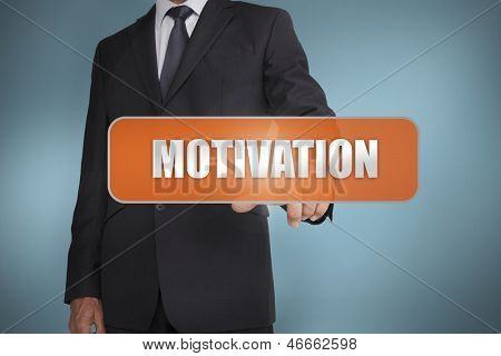 Businessman selecting the word motivation against blue background