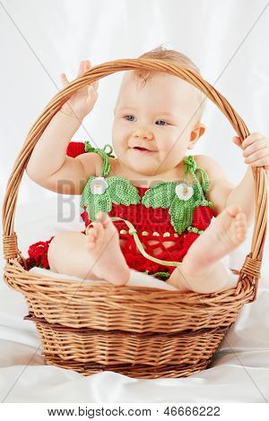 Portrait of smiling little girl dressed in strawberry suit sitting in wicker basket on white coverlet