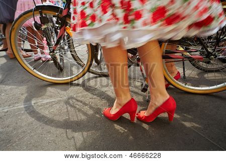 Female legs and bikes wheels, flowered skirt blurred in motion