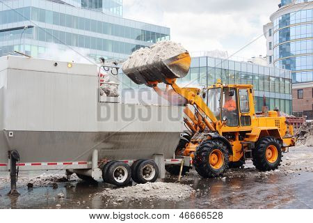 Bulldozer loads snow to truck for snow melting on street in city at cloudy day.