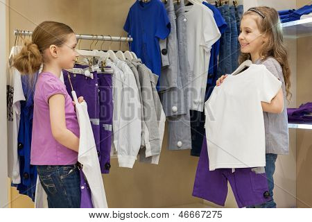 Two smiling little girls trying on the same dress in the store childrens clothes, focus on right girl