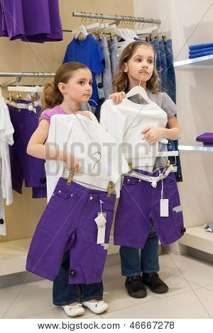 Two girls trying on the same dress in the store children clothes