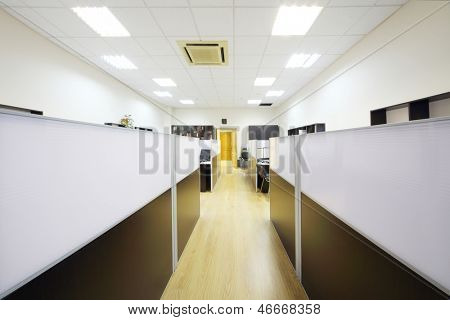 Corridor and empty working areas with desktops separated by partitions in office.