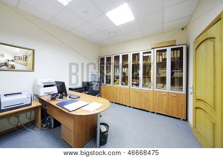 Empty working area with armchair and desktop and bookcase in modern office.