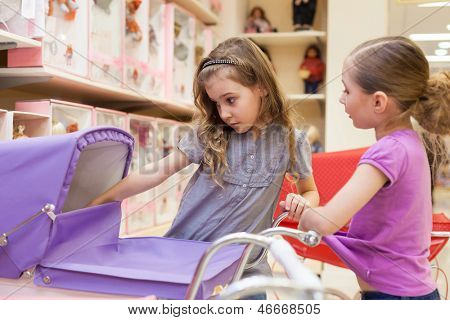 Two girls in a toy store with dolls look into the buggy, focus on left girl